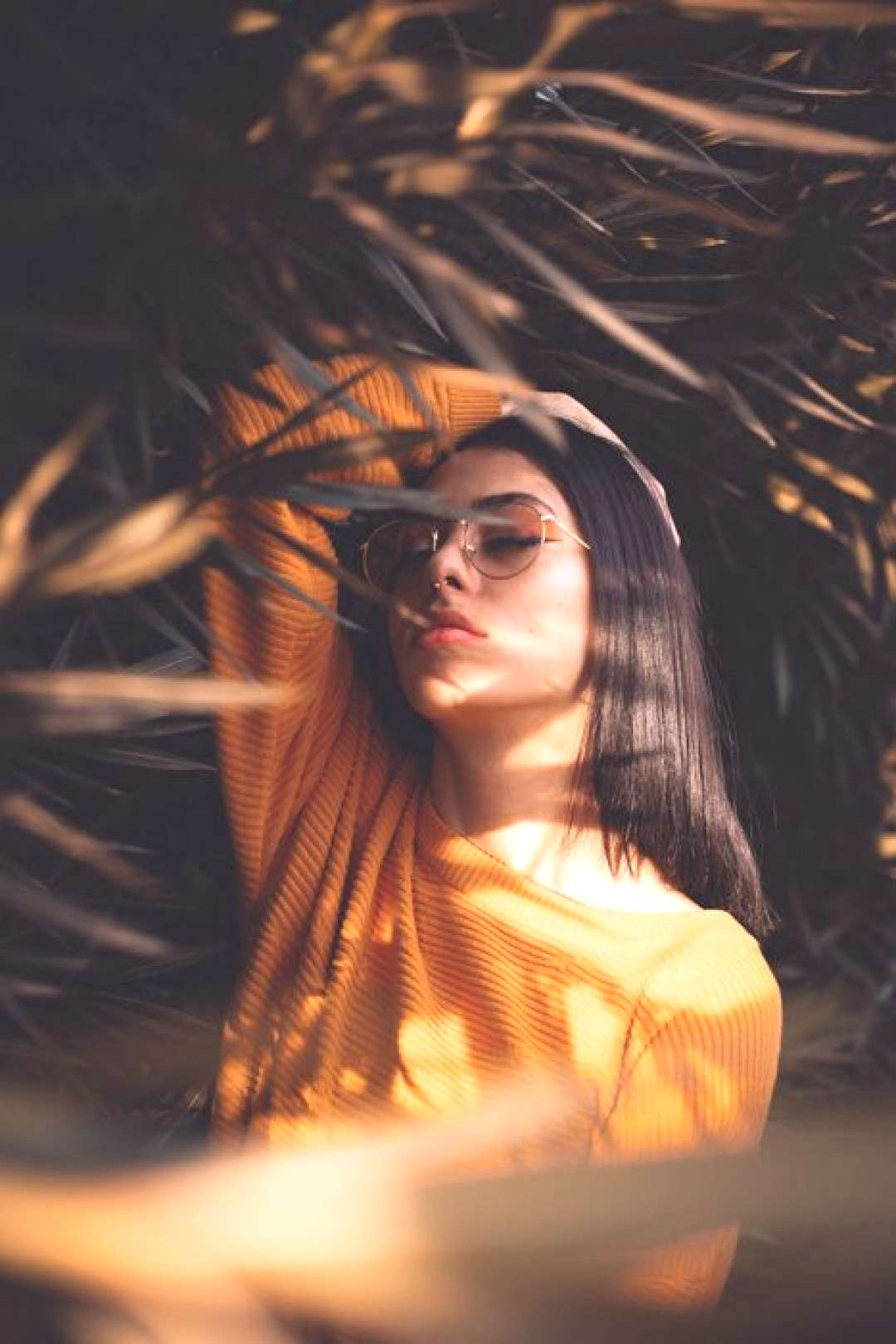 A portrait of a female model posing among foliage - best photography tutorials